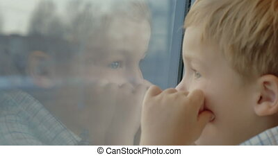 Little child enjoying view from the train window