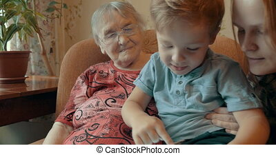 Boy playing on pad with mother and granmother