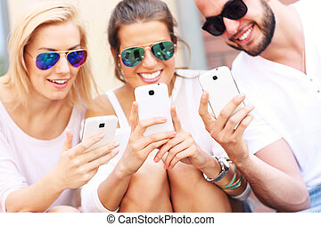 Group of friends using smart phones