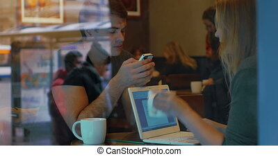 Young people with smart phone and laptop in cafe - Young...