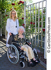 Young Nurse Assisting Elderly Woman on Wheelchair - Young...