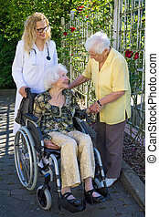 Elderly with her Doctor Talking to her Caregiver