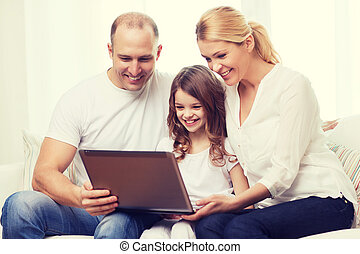 parents and little girl with laptop at home