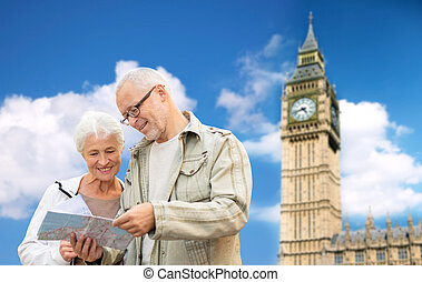 senior couple with map over london big ben tower - family,...