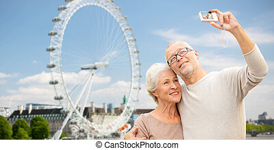 senior couple selfie with camera over london - age, tourism,...