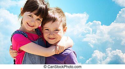 two happy kids hugging over blue sky and clouds