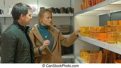 Couple in Utensil Shop - Young couple is choosing cups in...