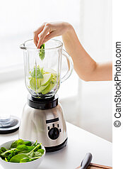 close up of woman hand with blender and vegetables - healthy...
