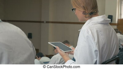 Medical student taking notes on pad during lecture - Female...