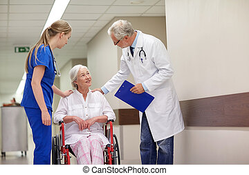 medics and senior woman in wheelchair at hospital -...