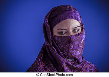Beautiful arabic woman with traditional veil on her face,...