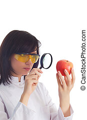 Female scientist looking at apple through magnifying lens