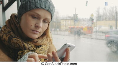 Woman texting on cell phone during bus ride in city - Young...