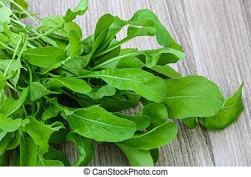 Ruccola - Fresh green Ruccola leaves heap on the wood...