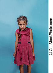 Girl European appearance decade angry frowns on blue...