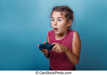 Girl European appearance decade holds a gaming joystick in...