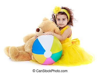 Little girl hugging Teddy bear - Fashionable curly...