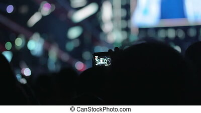 People on the Concert Taking Photos of the Stage - Man is...