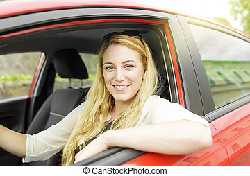 Woman in the car. - Pretty blonde woman driving a red car.