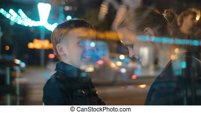 Happy mother and child talking in night city - Son and...