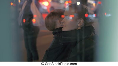 Tired boy giving hug to mother at bus stop - Mother and son...