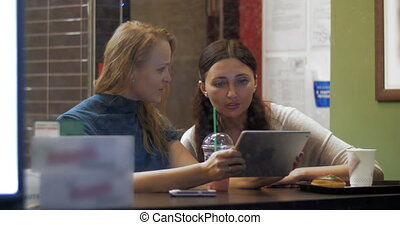 Friends Watching Photos in Tablet PC - Two female friends...