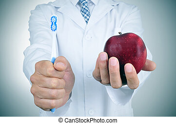 a dentist showing a toothbrush and an apple depicting the...