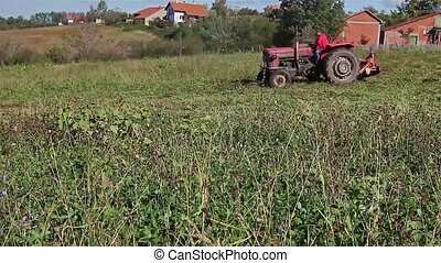 Agricultural activity - Farmer cutting grass with tractor...
