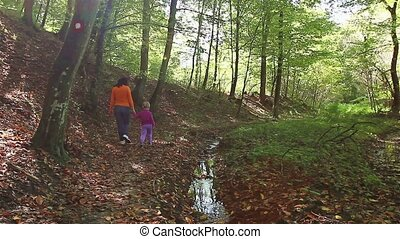 Walk trough forest. - Mother with her daughter is walking...