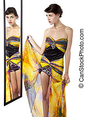 Woman Looking at Mirror - Woman wearing a yellow dress...