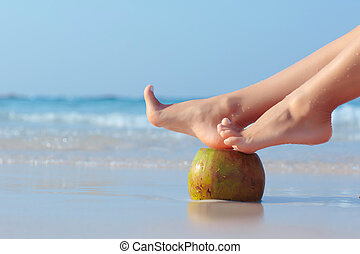 Female feet propped on coconut sea - Female feet propped on...