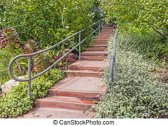 Garden path of red concrete steps with metal handrails...