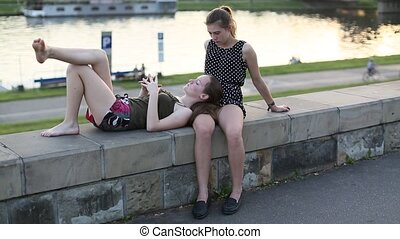 Two best friends teenage girls sitting and close talking on...