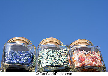 Pebble jewelry contained in three bottles under blue sky