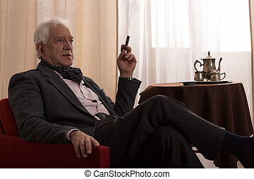 Old man's free time - Man enjoys his time and he is smoking...