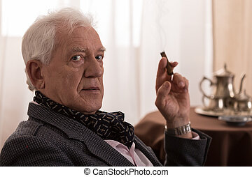 Nostalgic old man - Old man is nostalgic and he is smoking a...