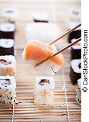 Eat sushi - a salmon nigiri sushi being picked up with...