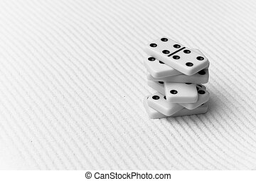 Dominoes against sand - The dominoes are piled against grey...