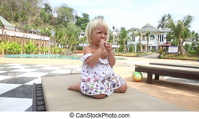 mother gives banana to little girl near pool