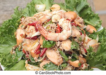 Spicy seafood noodle with green leafy vegetables.