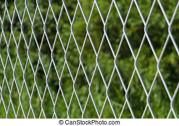 Blurred metallic mesh fence against green background