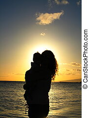 Silhouette, mother and child in tropics, sky and ocean