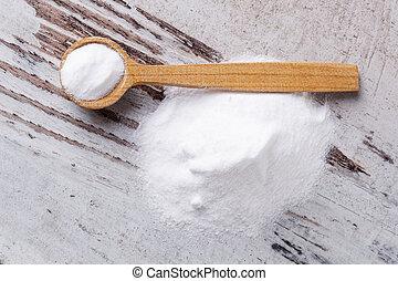 Baking soda. - Baking soda on wooden spoon on white wooden...