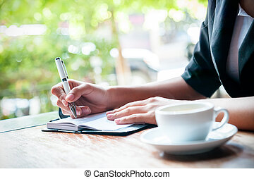 writing a journal - close up of woman writing journal and...
