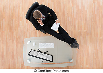 Businessman Reading Document In Office - Businessman Reading...