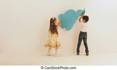Decorating A Wall - Boy and girl decorating a wall with...