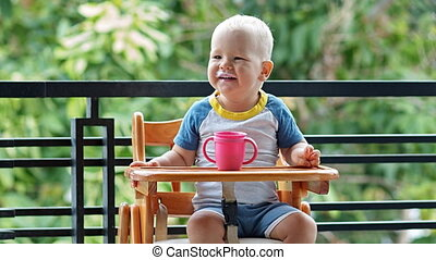 Toddler boy gives a smile while paused to drink a milk cup...