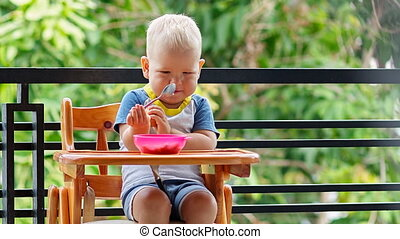 Toddler boy practice to eat with spoon sitting at the...
