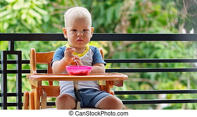 Toddler boy plays with food sitting at the highchair on the...