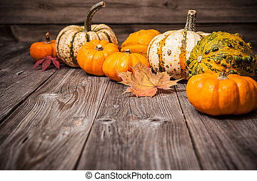 Autumn still life with pumpkins and leaves on old wooden...
